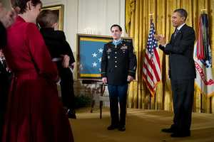 President Barack Obama applauds after awarding former Staff Sergeant Clinton Romesha the Medal of Honor for conspicuous gallantry during a ceremony in the East Room of the White House, Feb. 11, 2013. At left, Romesha's wife Tammy holds their 2-year-old son, Colin.