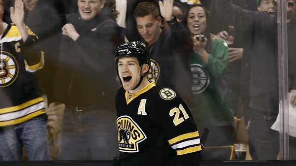 Fans celebrate with Boston Bruins' Andrew Ference after he scored against the Washington Capitals during the second period of an NHL hockey game in Boston, Saturday, March 16, 2013.