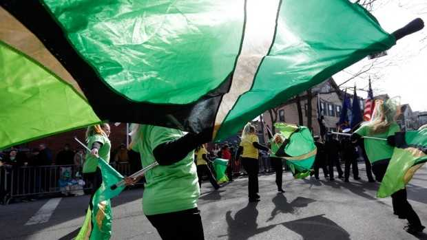 Women from the Sanford High School color guard, of Sanford, Maine, twirl green flags while marching in the St. Patrick's Day Parade in South Boston.