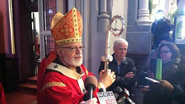 Cardinal Sean O'Malley talks with reporters at the Cathedral of the Holy Cross on Palm Sunday, March 24, 2013.