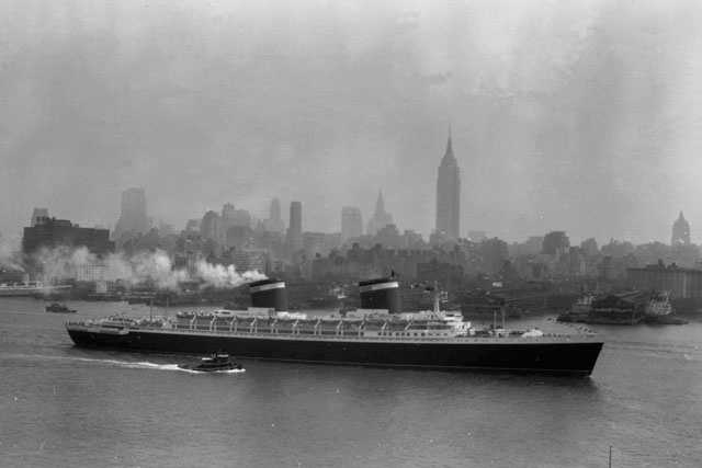 In this July 3, 1952 photo, the SS United States glides down the Hudson River as it begins its first voyage to Europe from New York in view of the Midtown Manhattan skyline including the Empire State building on the center right.