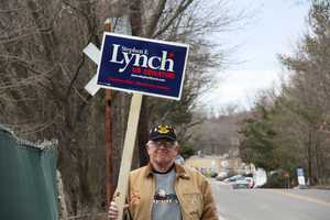 A supporter of Stephen Lynch carries his sign before the debate.