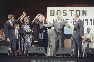 Nelson Mandela, center, dances to African folk music during the rally and concert at the Hatch Shell on Boston's Esplanade, June 23, 1990. Mandela was joined by U.S. Senator Edward Kennedy, left, and Boston Mayor Ray Flynn.