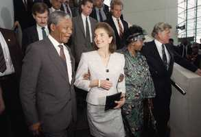 Jacqueline Kennedy Onassis casts a smiling glance at Nelson Mandela, deputy president of the African National Congress, during Mandela's visit to the John F. Kennedy Library on June 23, 1990 in Boston. The Kennedy family has been a longtime opponent of South Africa's policy of apartheid.
