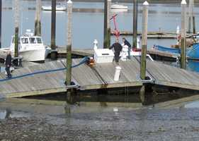 Fire officials said because of the extremely low tide overnight, the boat somehow got wedged underneath the dock causing it to take on water and tip.