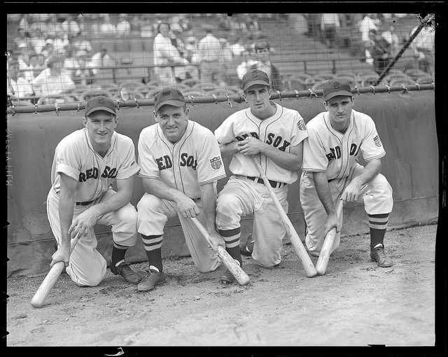 Boston Red Sox Jim Tabor, Tony Lupien, Johnny Pesky, and Bobby Doerr kneeling in front of the screen at Fenway Park in 1942.