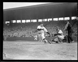 Boston Red Sox batter Bobby Doerr smashes one in front of New York Yankees catcher Bill Dickey at Fenway Park.