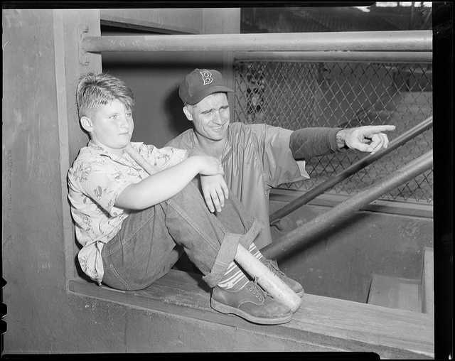 Unknown young boy sitting on dugout wall as Boston Red Sox Bobby Doerr points toward the field in 1951.