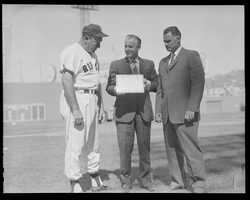 (L to R:) Boston Red Sox coach Rudy York accepts award from Red Sox broadcaster Curt Gowdy as former Red Sox Bobby Doerr looks on at Fenway Park in 1962.