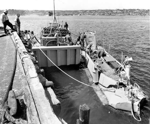 Sailor run lines from a barge to pump ballast from the navy bathyscaph (deep-sea boat) Trieste at San Diego. It will be taken by railroad flat car to the Atlantic to aid the search for missing atomic submarine Thresher, April 11, 1963.