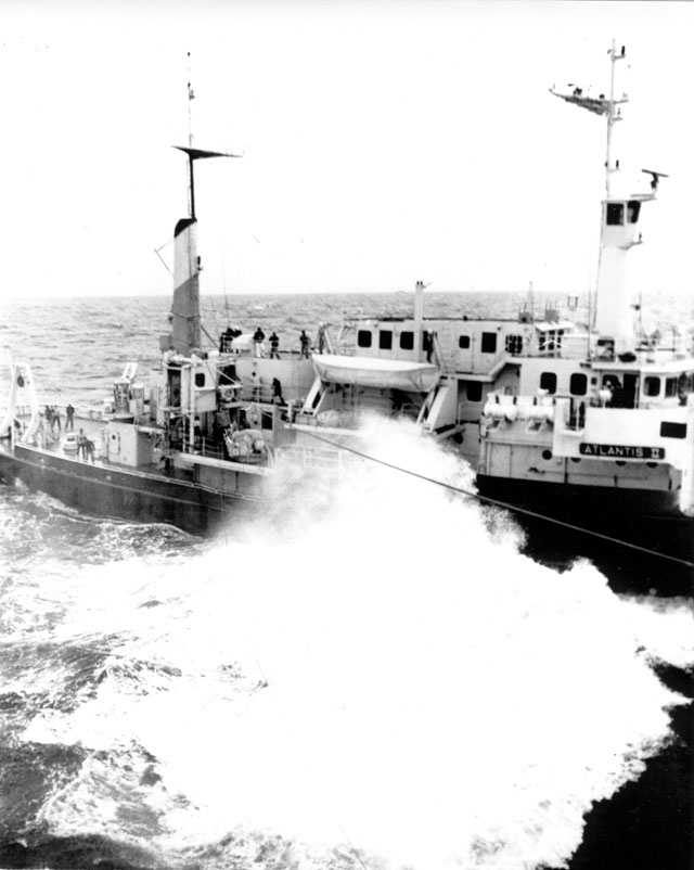 High sea breaks against the port side of the research vessel Atlantis II, April 14, 1963, as a breeches buoy is rigged up with destroyer Hazelwood for the transfer of sonar equipment to seek the grave of missing submarine Thresher.