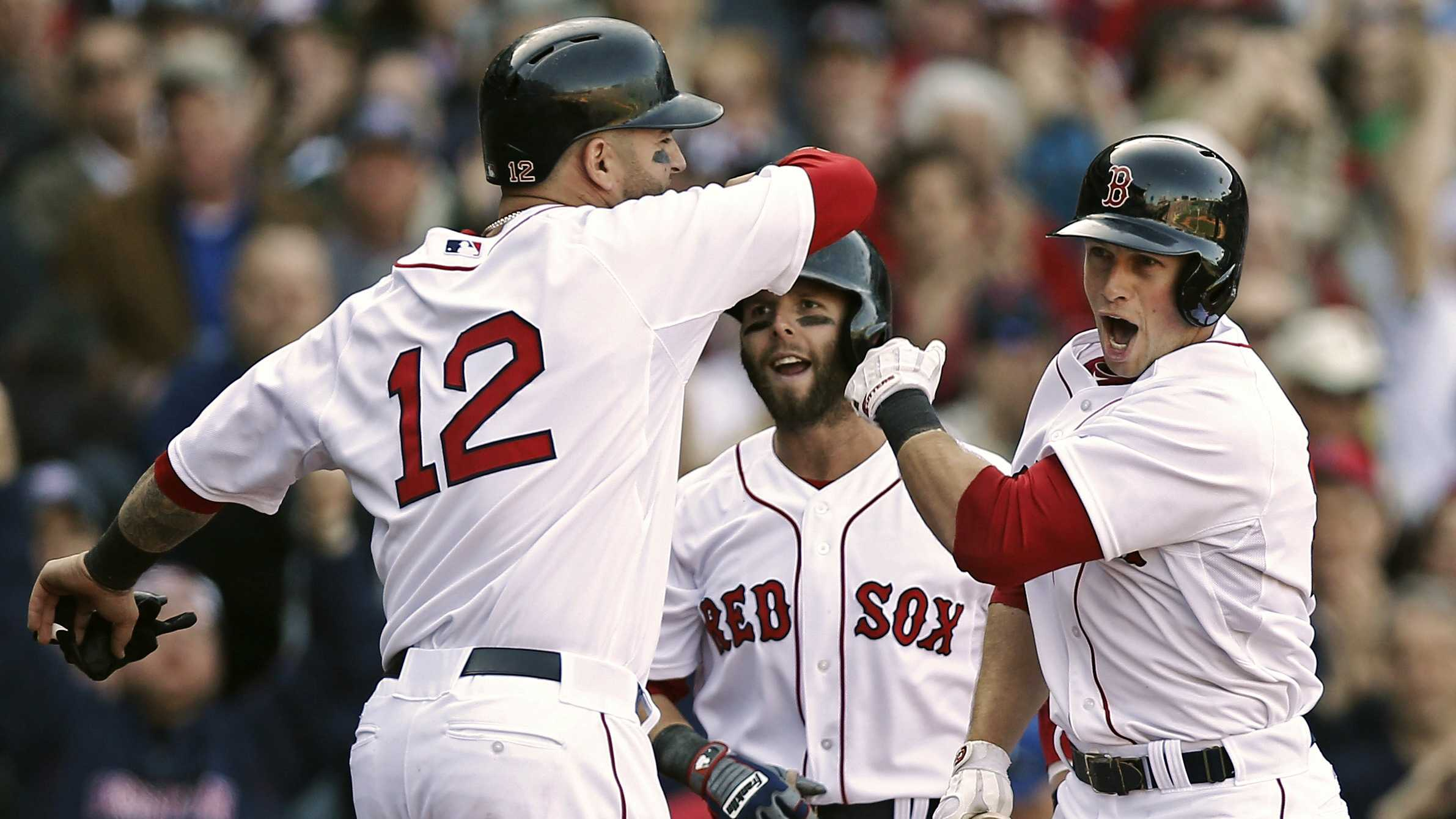 Daniel Nava, right, is greeted by Dustin Pedroia and Mike Napoli (12) after hitting a three-run home run during the seventh inning against the Baltimore Orioles at Fenway Park, April 8, 2013.