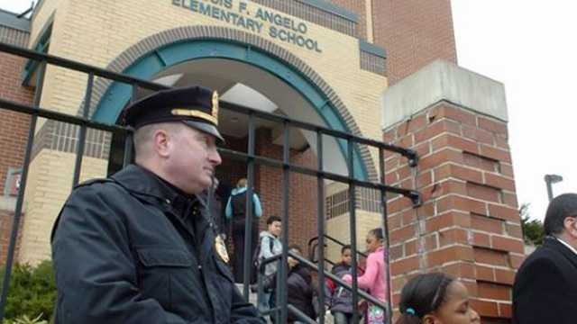 Brockton police Lt. Donald Mills stands guard at the front entrance at the Angelo School in March 2011. A BB gun was fired in the school playground and on a bus by an 11-year-old student