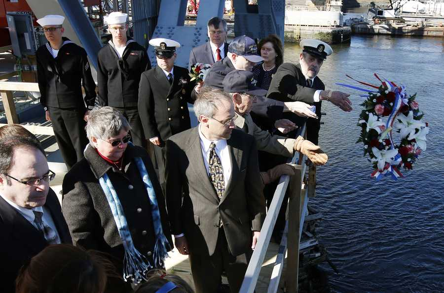 Family, veterans and current service members take part in a wreath ceremony to mark the 50th anniversary of the sinking of the USS Thresher on the Memorial Bridge in Portsmouth, N.H.