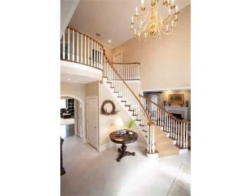 Dramatic 2-story foyer with a sweeping staircase leads to formal dining room & fireplaced living room.