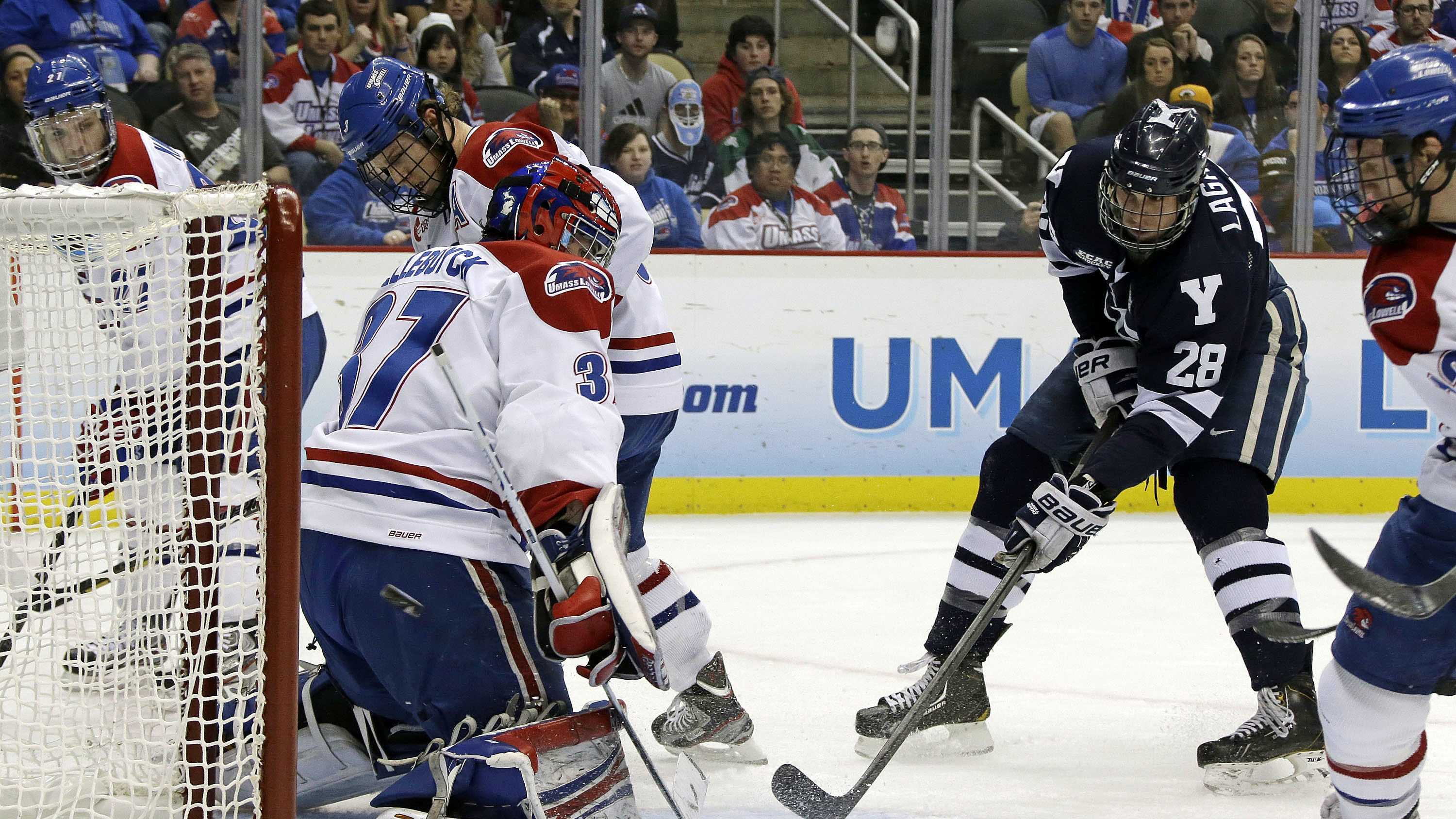 Yale right wing Antoine Laganiere (28) gets the puck behind UMass Lowell goalie Connor Hellebuyck (37) during the first period of an NCAA college hockey game in Pittsburgh, April 11, 2013.