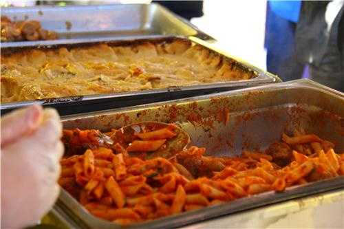 Volunteers serve up pasta and other carb-heavy foods to the runners.