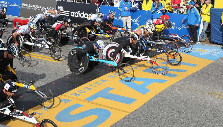 Defending champion Joshua Cassidy, of Canada, fifth front right, starts the wheelchair division of the 117th running of the Boston Marathon