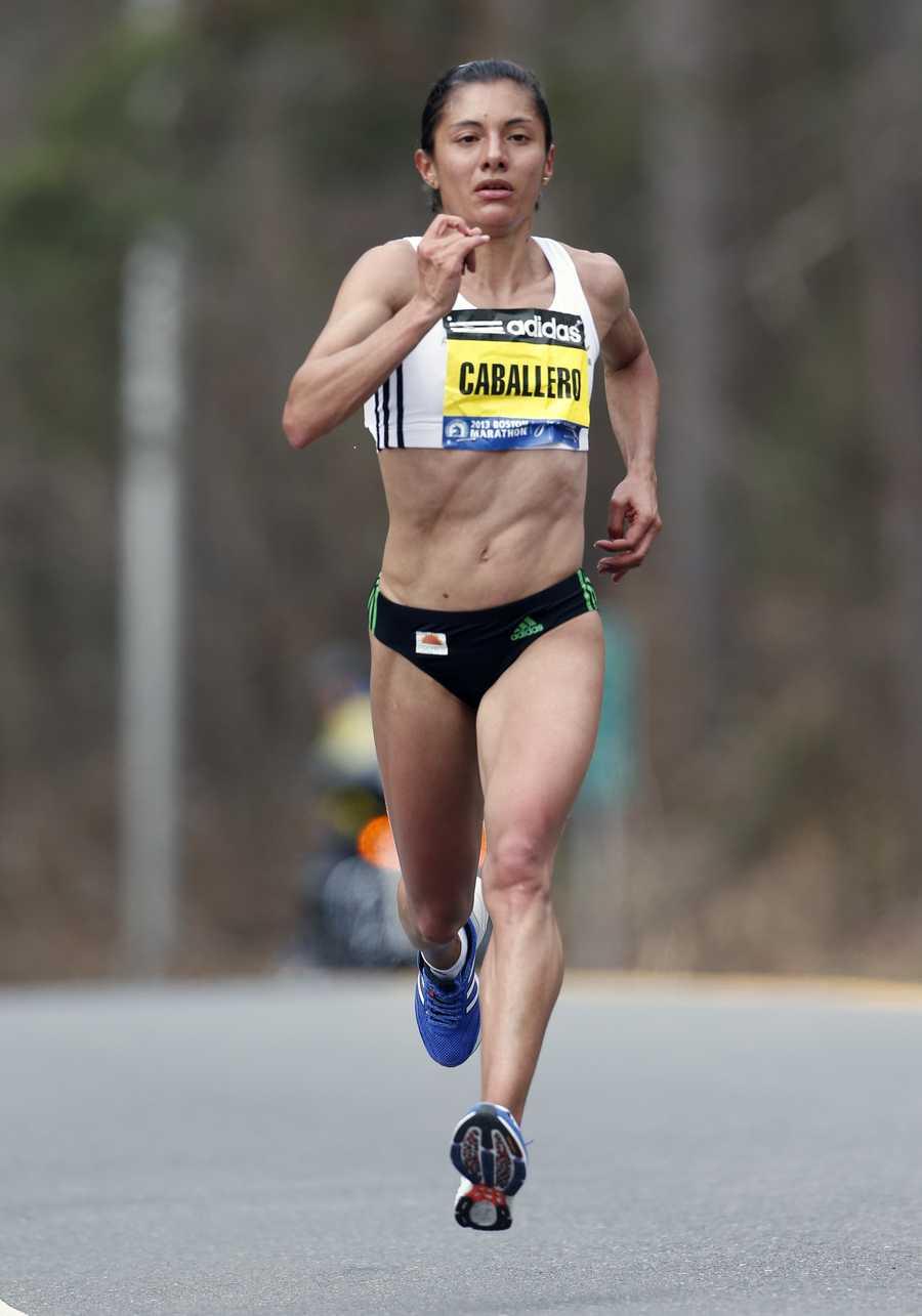 Yolanda Caballero runs alone at the twelve-mile mark on the Boston Marathon course in Wellesley
