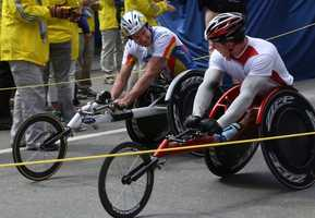 Krige Schabort, left, and Tomasz Hamerlak, right, crossed the finish line of Boston Marathon just seconds apart. No longer competing the two men congratulated each other after finishing the Men's Wheelchair race at the Boston Marathon.