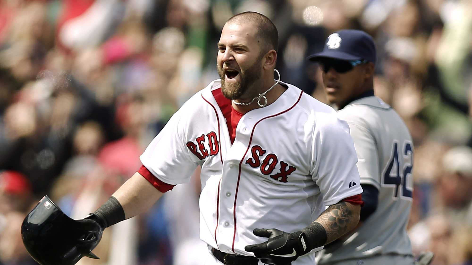 Boston Red Sox's Mike Napoli celebrates after his game-winning double as Tampa Bay Rays' Yunel Escobar watches during the ninth inning of a baseball game at Fenway Park in Boston on Monday, April 15, 2013. Boston won 3-2.