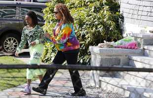 Jacqueline Myers and her daughter Amira, 10, depart after leaving flowers on the doorstep of the Richard house in the Dorchester neighborhood of Boston,Tuesday, April 16, 2013. Martin Richard, 8, was killed in Mondays bombing at the finish line of the Boston Marathon.