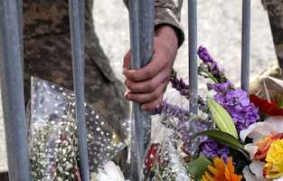 A Massachusetts National Guard member adjusts a barrier near a makeshift memorial on Boylston Street near the site where a day earlier explosions killed three and injured more than 170 in Boston.