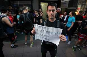 """A runner shows a banner reading: """"Boston we are with you - Belgrade runners"""" in an organized memorial run to show solidarity with victims of the Boston Marathon bombing in Belgrade, Serbia."""