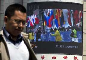 A Chinese man walks past a huge screen which reports the Boston Marathon bombings that killed three and wounded more than 170 people, in Beijing, China Wednesday.