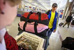 Matthew Gibbs, right, of Cochran, Ga., stands with his mother-in-law Linda Dykes, left, as she looks at a newspaper he brought her from Boston as he arrives at Hartsfield-Jackson airport after running in the Boston Marathon in Atlanta.
