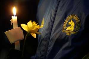 Lizzie Lee, 56, of Lynwood, Wash., who was participating in her first Boston Marathon and 11th overall, holds a candle and a flower at Boston Common during a vigil for the victims of the Boston Marathon explosions.