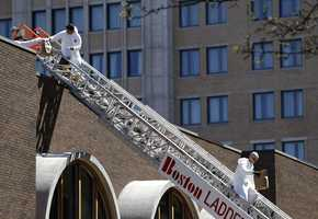 FBI investigators walk down a fire truck ladder with bags from a building at the corner of Boylston Street and Fairfield Street , Wednesday.