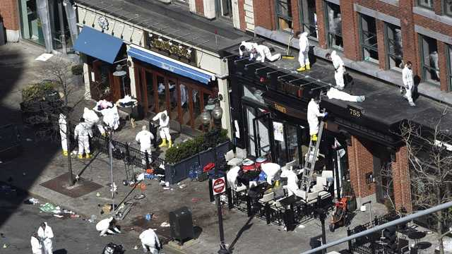 Investigators comb through the scene of one of the blast sites of the Boston Marathon explosions, Wednesday