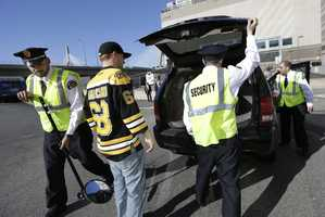 A fan, center, watches as security officers check his vehicle on the way into TD Garden prior to a Boston Bruins hockey game against the Buffalo Sabres in the aftermath of Monday's Boston Marathon bombings.
