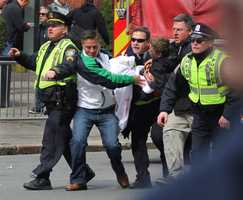 Emergency personnel carry a wounded person away from the scene of an explosion at the 2013 Boston Marathon in Boston.