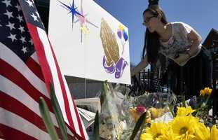 Shannon Walsh, 15, places flowers on a memorial to Boston Marathon bombing victim, Martin Richard, 8, near the Richard family house in the Dorchester neighborhood of Boston.