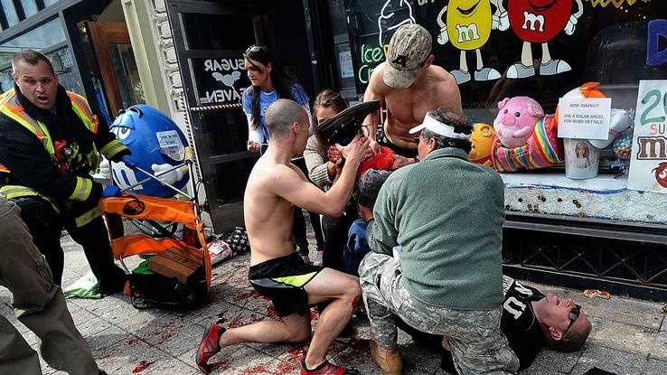 Robert Wheeler, of Ashland, a Framingham State University student and Boston Marathon runner, kneeling at left, helps a man injured after after explosions at the Boston Marathon finish line.