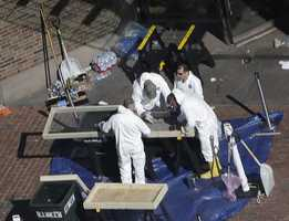 Investigators inspect the area between the two blast sites near the Boston Marathon finish line Thursday.