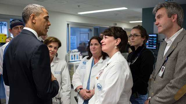 President Barack Obama talks with staff at Massachusetts General Hospital in Boston