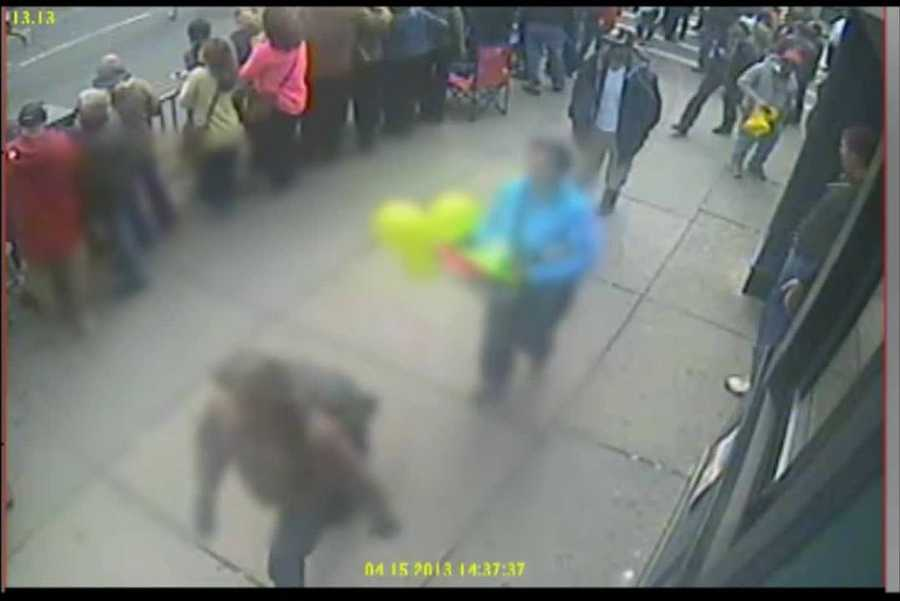 In surveillance video released by the FBI, a woman carrying balloons down Boylston Street was also captured on camera. She is blurred out in this video frame taken at 2:37:37 p.m. on April 15.
