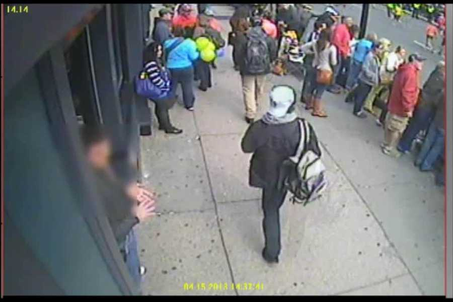 The video shows the suspects continuing to walk down Boylston Street, while the woman with the balloons appears to stop.
