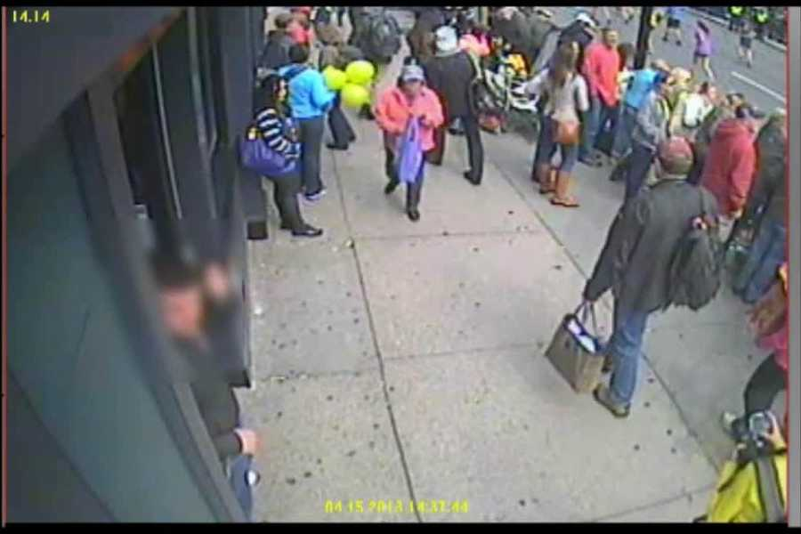 Suspect #2 (with the white hat) is seen continuing to walk down Boylston Street, past the woman with the ballons.