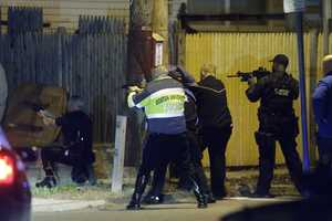 Police officers aim their weapons Friday, April 19, 2013, in Watertown, Mass. A tense night of police activity that left a university officer dead on campus just days after the Boston Marathon bombings and amid a hunt for two suspects caused officers to converge on a neighborhood.