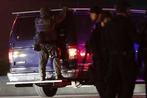 A police officers rides on the back of a van at a staging area as a manhunt is conducted for a suspect Friday, April 19, 2013, in Watertown, Mass. One of two suspects in the Boston Marathon bombing is dead and a massive manhunt is underway for another, authorities said early Friday April 19, 2013. Residents of Watertown, a Boston suburb, have been advised to keep their doors locked and not let anyone in.