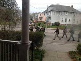 Police conduct door-to-door searches in Watertown.