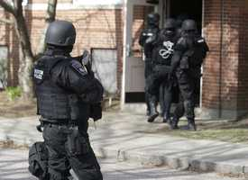An official wearing tactical gear, left, looks on as others enter an apartment building in Watertown, Mass., Friday, April 19, 2013.