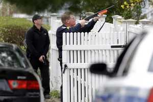 A police officer points his weapon at a residence as he conducts a search for a suspect in the Boston Marathon bombings, Friday, April 19, 2013, in Watertown, Mass.