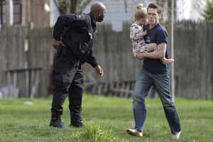 A police officer evacuates a shoeless man holding a child as members of law enforcement conduct a search for a suspect in the Boston Marathon bombings, Friday, April 19, 2013, in Watertown, Mass.