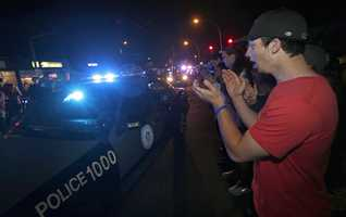 A man applauds as police leave the scene of the arrest of a suspect of the Boston Marathon bombings.