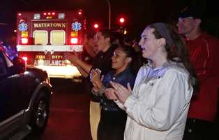A gathering of people applaud as first responders leave the scene.